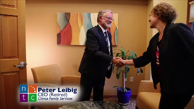 Image from the Primary Care Partnership Video of a middle-aged man and woman in a cozy office shaking hands.